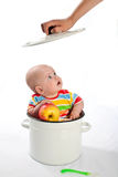 Baby with apple in the big saucepan. Stock Photo