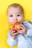 Baby with apple Stock Images