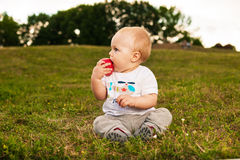 Baby with apple outdoors. Smiling beautiful baby looking at camera and eating apple outdoors in sunlight Royalty Free Stock Photo