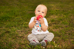 Baby with apple outdoors. Smiling beautiful baby looking at camera and eating apple outdoors in sunlight Stock Photography