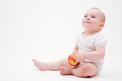 Baby with apple sitting on the floor Stock Photos