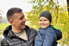Baby on arms of his father in park.  stock images