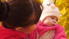 Baby is in the arms of mother in park in fall. stock video footage