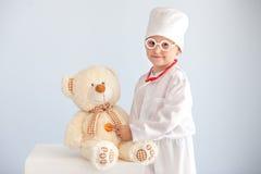 Baby arts, medisch beroep, arts, geneeskunde, gezondheidszorg, eenvormige arts, kind in witte toga, jongen arts, uniphorm Royalty-vrije Stock Foto