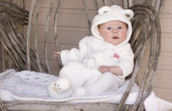Baby As A Bear. An adorable baby with blue eyes, wearing a bear suit, sits in a rustic chair Stock Images