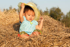 Baby of Asia sits on straw Stock Photography