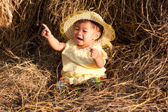 Baby of Asia sits in straw Royalty Free Stock Photography