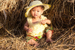 Baby of Asia sits in straw Stock Photography