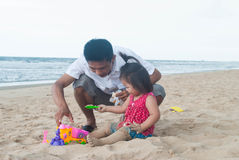 Baby asian girl with father playing on the beach. Royalty Free Stock Images