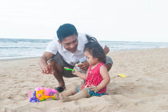 Baby asian girl with father playing on the beach. Stock Photography