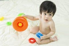 Baby Asien und Spielzeug auf Bett Stockfoto