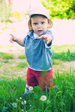 Baby asking help. Young baby sanding in grass with hand stretched, asking for help Stock Images