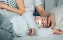 Baby asleep while parents caress. Baby asleep while his parents caress him Royalty Free Stock Images