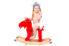 Baby in Asterix hat on the toy elk Royalty Free Stock Photography