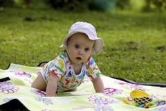 Baby auf dem Picknickteppich im Gras Lizenzfreies Stockfoto