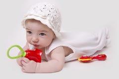 Baby auf dem weißen Spielen mit Geklapper Lizenzfreie Stockbilder