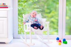 Baby auf einem Schaukelstuhl Stockfotos