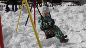 Baby auf Schwingenfahrt im Winter stock video footage
