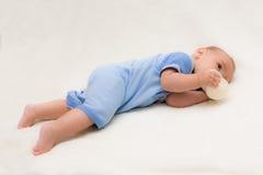 Baby auf trinkender Flasche des Bauches Stockfotografie