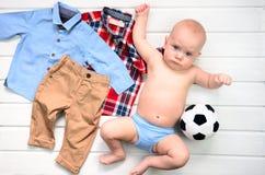 Baby auf weißem hölzernem Hintergrund mit Kleidung und Fußball spielen stockfotos