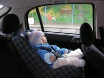 Baby in auto met dromen in venster stock foto's