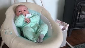 Baby in Automatic Rocker. A little baby girl in an automatic rocker at home stock video footage
