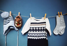 Baby autumn or winter fashion concept background. Autumn or winter children's outfit clothes hanging on the clothesline on a textured wall background with copy stock photography