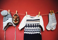 Baby autumn or winter fashion concept background. Autumn or winter children's outfit clothes hanging on the clothesline on a textured wall background with copy stock image