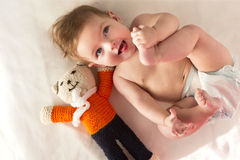 Baby Is Awake. Playful baby lying with a diaper and Teddy Stock Images