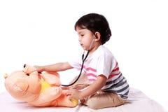 Baby bärande stetoskop och speladoktor Arkivbild