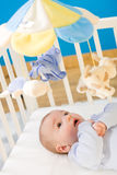 Baby in baby bed Stock Images