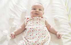 Baby in a baby bed. White clothes. Window light Stock Photos