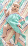 Baby in a baby bed. White clothes. Window light Royalty Free Stock Image