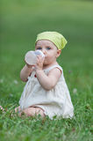 Baby with baby bottle. Baby drinking by her baby bottle on a field Royalty Free Stock Images