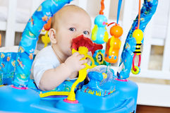 Baby in baby jumper. Funny baby is playing in baby jumper Stock Photography