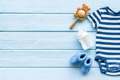 Baby background - blue color. Clothes and accessories for newborn boy on blue wooden table top-down frame copy space