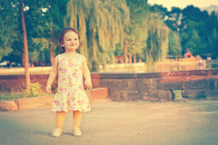A baby on the background of nature. Child near the lake. Kid walking on the street in the summer. Summer scene with little girl Stock Photos
