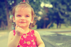 A baby on the background of nature. Happy smiling child. Laughing kid walking on the street in the summer. Royalty Free Stock Images