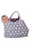 Baby in bag. Baby girl in a bag looks dreamily royalty free stock image