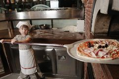 Baby baker puts pizza into the wood-burning stove Royalty Free Stock Image