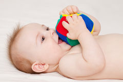 Baby with ball. Cute baby lying and playing with a ball Stock Images