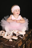 Baby Ballerina. Sitting on an antique trunk Royalty Free Stock Photo