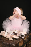 Baby Ballerina. Sitting on an antique trunk Royalty Free Stock Image