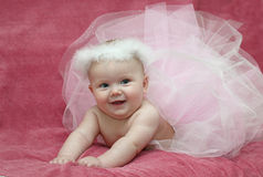 Baby ballerina. In pink dress lying on pink background smiling Stock Images
