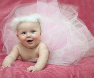 Baby ballerina. Baby in ballet dress lying on pink background Royalty Free Stock Photography