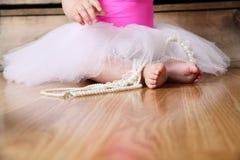 Baby ballerina feet. On a wooden floor in white tutu Stock Photography