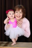 Baby ballerina. Grandmother and ballerina baby portrait against brown Royalty Free Stock Photography