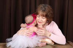 Baby ballerina. Grandmother and ballerina baby portrait against brown Stock Images