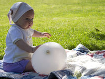Baby with ballon. Ittle baby in the garden with white ballon Stock Images