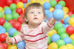Baby with balls. Portrait of beatiful baby girl with vivid balls Stock Photos